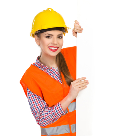 lumberjack shirt: Smiling young woman in yellow hardhat, orange reflective vest and lumberjack shirt standing behind big white banner and holding it. Waist up studio shot isolated on white.