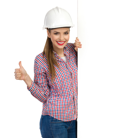 lumberjack shirt: Smiling beautiful young woman in white hardhat and lumberjack shirt standing, holding big white banner and showing thumb up. Waist up studio shot isolated on white. Stock Photo