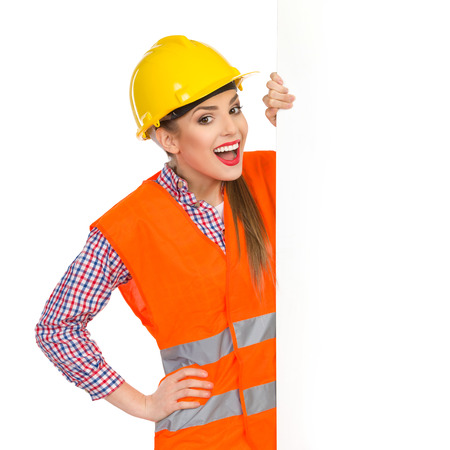 lumberjack shirt: Excited young woman in yellow hardhat, orange reflective vest and lumberjack shirt standing behind big white banner and holding it. Waist up studio shot isolated on white.