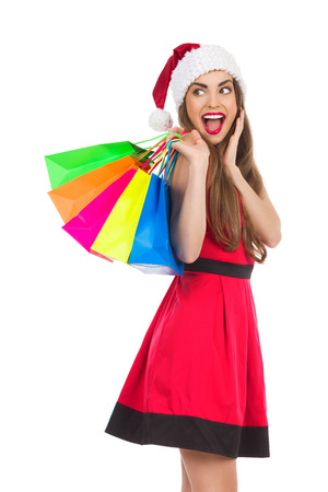 sideways glance: Christmas girl with colorful shopping bags holding hand on chin, shouting and looking over shoulder. Three quarter length studio shot isolated on white.