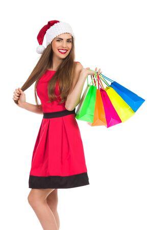 three quarter length: Christmas girl holding colorful shopping bags. Three quarter length studio shot isolated on white.