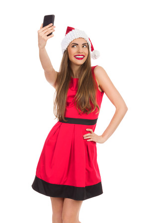 three quarter length: Beautiful young woman in red santas hat and dress taking a selfie. Three quarter length studio shot isolated on white.