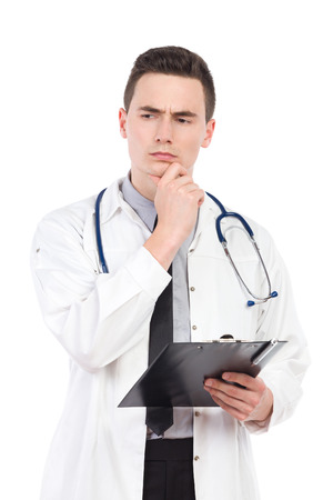three quarter length: Thinking young male doctor holding a clipboard. Three quarter length studio shot isolated on white.