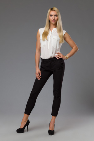 platinum hair: Young blond woman in white shirt, black pants, and high heels standing with hand on hip and looking at camera. Full length studio shot on gray background.