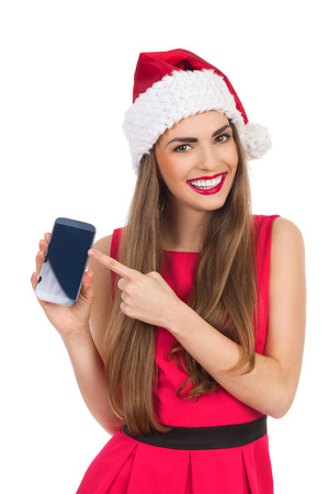 waist shot: Beautiful young woman in red santas hat and dress pointing at mobile phone. Waist up studio shot isolated on white.