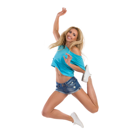 persona saltando: Blond young woman in jeans shorts, turquoise top and white sneakers jumping with arm raised and smiling. Full length studio shot isolated on white. Foto de archivo