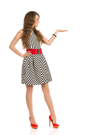 ab7513ab77  56504435 - Sonriente mujer atractiva en blanco y negro a rayas vestido y  tacones altos posando con la mano planteada y mostrando algo