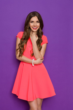 three quarter length: Elegance young woman in pink mini dress posing with hand on chin and looking at camera. Three quarter length studio shot on purple background.