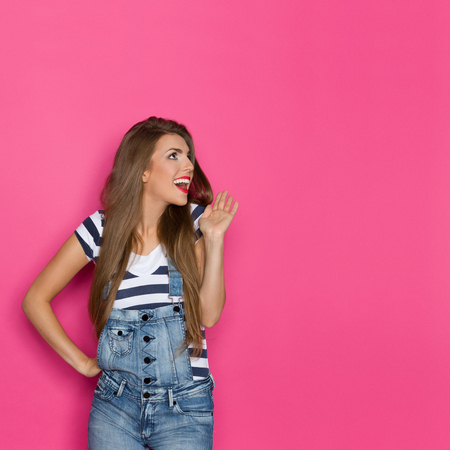 three quarter: Beautiful shouting young woman in dungarees and blue striped shirt looking away at copy space. Three quarter length studio shot on pink background.