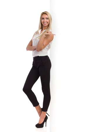 is based: Elegance blond woman in black pants, white shirt and high heels standing based on a big white banner and pointing. Full length studio shot isolated on white.