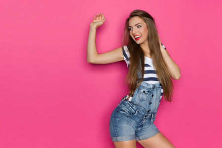 dungarees: Ecstatic young woman in dungarees and blue striped shirt looking away. Three quarter length studio shot on pink background.