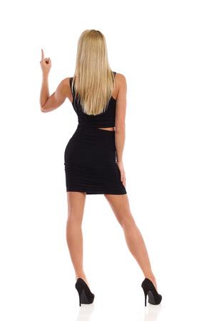 mini skirt: femme blonde Attractive en mini jupe noire et hauts talons pointant vers le haut. Vue arriere. La pleine longueur tourn� en studio isol� sur blanc.