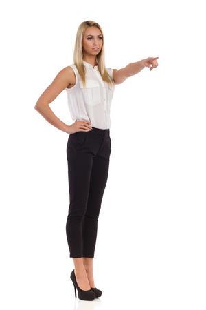 black pants: Elegance blond woman in black pants, white shirt and high heels standing, pointing and looking away. Full length studio shot isolated on white.
