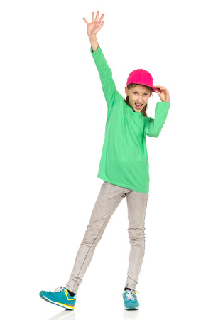 legs apart: Smiling girl in pink full cap, green blouse, jeans and sneakers standing with legs apart and waving hand. Full length studio shot isolated on white. Stock Photo