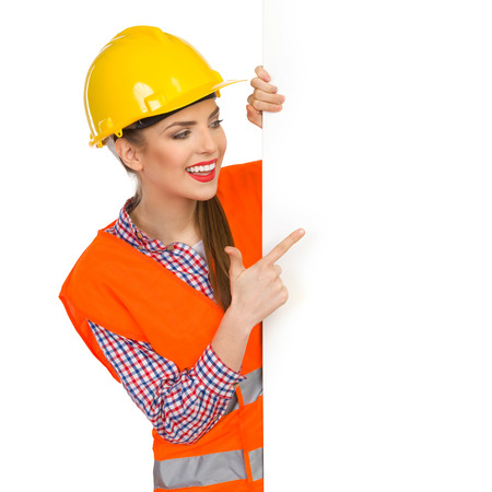 lumberjack shirt: Smiling young woman in yellow hardhat, orange reflective vest and lumberjack shirt standing behind big white banner and pointing. Waist up studio shot isolated on white. Stock Photo
