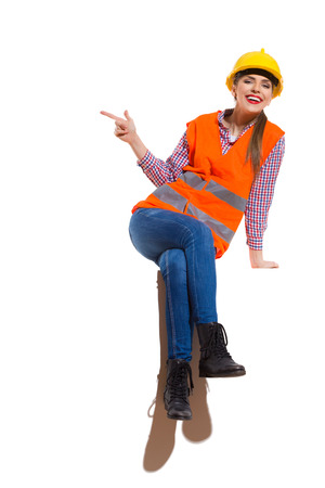 reflective vest: Smiling young woman in yellow hardhat, orange reflective vest, lumberjack shirt, jeans, black boots, sitting on top and pointing. Full length studio shot isolated on white. Stock Photo