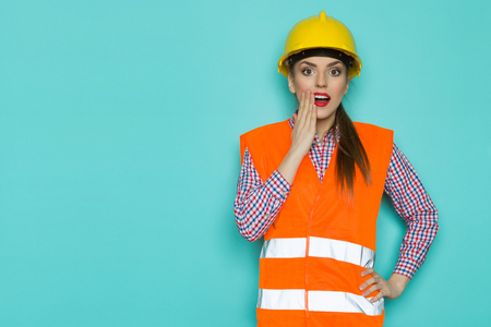 reflective vest: Surprised young woman in orange reflective vest and yellow hardhat holding hand on chin. Waist up studio shot on turquoise background.