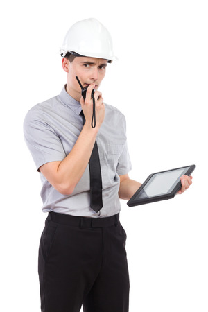 three quarter length: Engineer with digital tablet using walkie talkie. Three quarter length studio shot isolated on white. Stock Photo