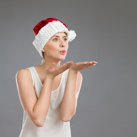 waist shot: Portrait of a female in santas hat sending a kiss. Waist up studio shot on gray background. Stock Photo