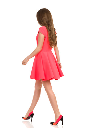 striding: Young woman in pink mini dress and high heels walking, Rear side view. Full length studio shot isolated on white.