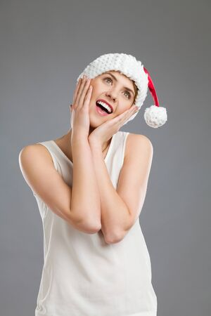 waist shot: Excited female in santas hat holding head in hands. Waist up studio shot on gray background.