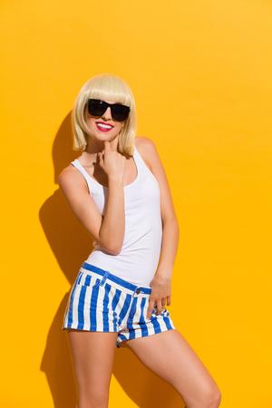 three quarter: Beautiful blonde girl posing in a black sunglasses. Three quarter length studio shot on yellow background.