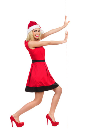 Smiling christmas girl in red dress, santa hat and high heels pushing a wall and looking at camera. Full length studio shot isolated on white. Stock Photo