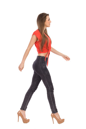 Young girl walking in red top, black jeans and high heels. Side view. Full length studio shot isolated on white. Stock Photo