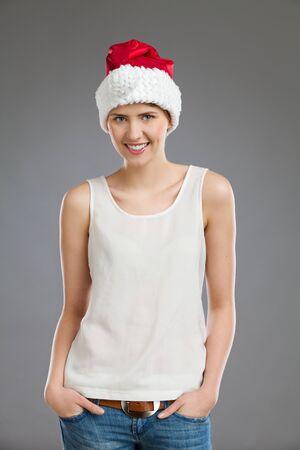 waist shot: Portrait of a female in santas hat. Waist up studio shot on gray background.