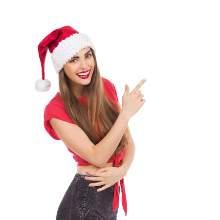 waist shot: Beautiful young woman in santas hat pointing. Waist up studio shot isolated on white.