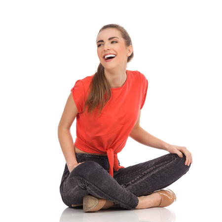 legs crossed at knee: Laughing girl in red top, black jeans is sitting on the floor with legs crossed and looking away. Full length studio shot isolated on white. Stock Photo