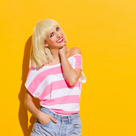 three quarter length: Smiling beautiful blonde young woman. Three quarter length studio shot on yellow background.