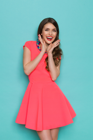 three quarter length: Excited beautiful young woman in pink mini dress posing with hands on chin. Three quarter length studio shot on turquoise background.