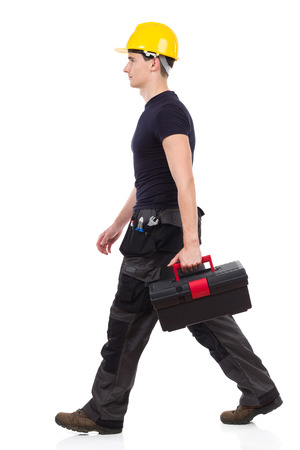 stride: Manual worker walking with toolbox and looking away. Full length studio shot isolated on white. Stock Photo