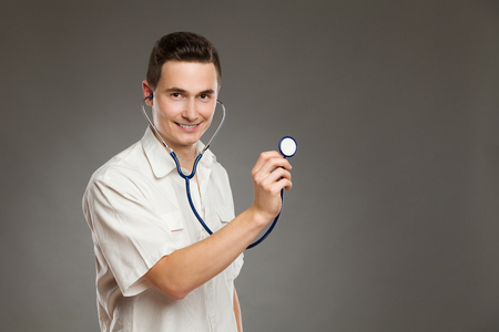 waist shot: Portrait of a smiling male doctor using stethoscope and listening. Waist up studio shot on gray background.