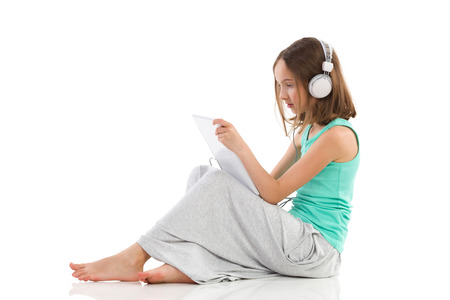 Little girl sitting on the floor, using a digital tablet and listening to the music. Side view. Full length studio shot isolated on white.