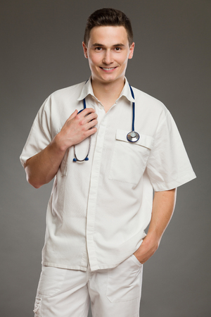 three quarter: Portrait of a smiling male doctor with hand in pocket. Three quarter length studio shot on gray background.
