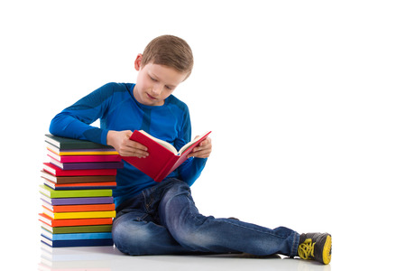 Schoolboy sitting on the floor close to the stack of books and reading one of them. Full length studio shot isolated on white. Stock Photo
