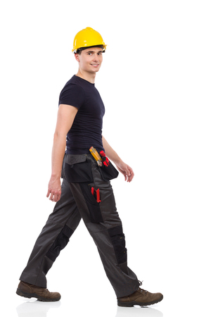 Manual worker walking and looking at camera. Full length studio shot isolated on white. Standard-Bild