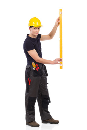 profile measurement: Manual worker measuring. Side view. Full length studio shot isolated on white.