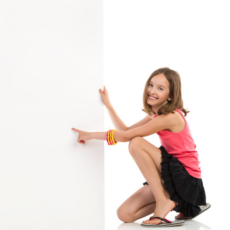preadolescence: Cute girl kneeling near blank banner and pointing. Full length studio shot isolated on white. Stock Photo