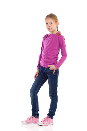 preadolescence: Little girl posing with hand in pocket. Full length studio shot isolated on white.