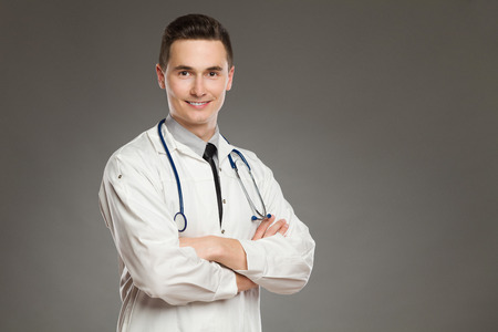 waist shot: Portrait of a doctor with arms crossed. Waist up studio shot on gray background.
