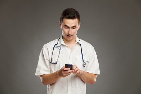 waist shot: Portrait of a surprised doctor using mobile phone and readng text message. Waist up studio shot on gray background.