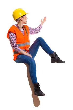reflective vest: Young woman in yellow hardhat, orange reflective vest, lumberjack shirt, jeans, black boots, sitting on top, looking away and presenting. Full length studio shot isolated on white.