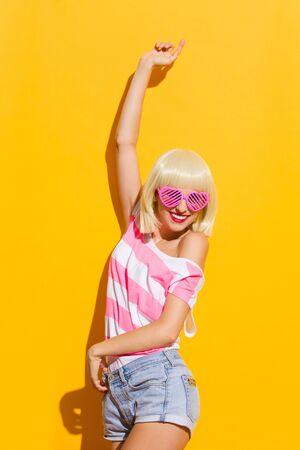 three quarter length: Beautiful blond summer girl in pink sunglasses posing with arm raised. Three quarter length studio shot on yellow background.