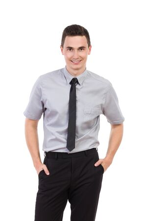 three quarter: Happy young man waiting with hands in pockets. Three quarter length studio shot isolated on white.