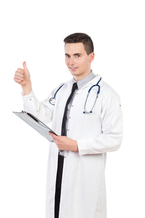 three quarter length: Young male doctor holding a clipboard and showing thumb up. Three quarter length studio shot isolated on white.