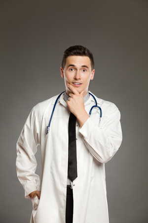 waist shot: Portrait of a surprised doctor with hand on chin. Waist up studio shot on gray background.