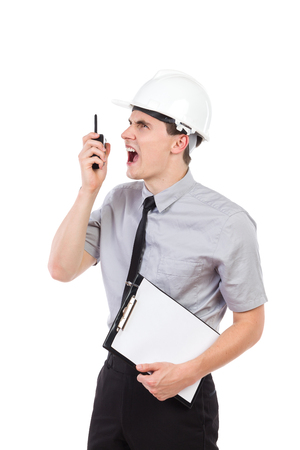 walkie talkie: Shouting engineer using walkie talkie, holding a clipboard and looking away. Waist up studio shot isolated on white.